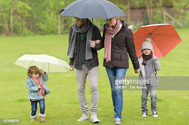 Family with umbrellas in a park