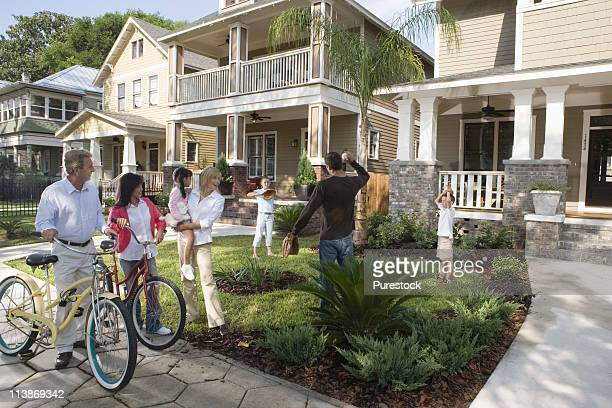 Family with young children conversing with neighbors in front of house