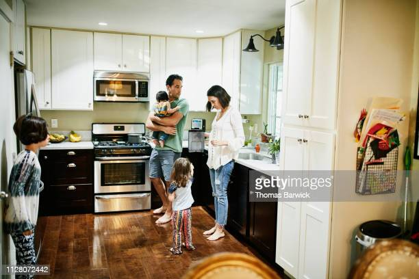 Family with young children preparing breakfast in kitchen