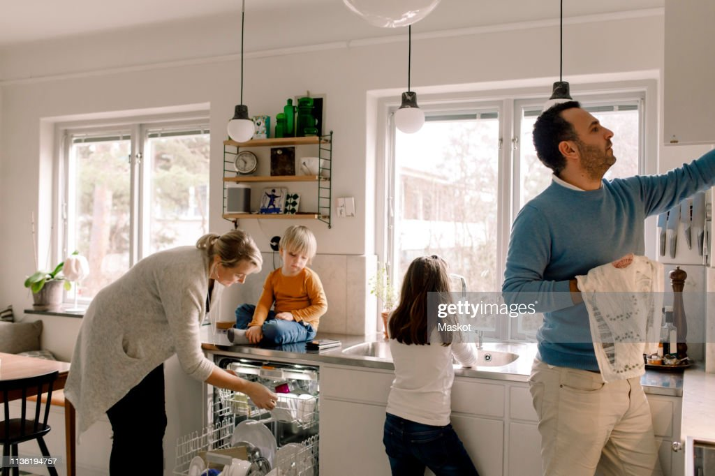 Family working in kitchen at home : Stock Photo