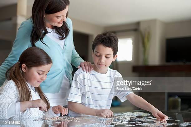 family working on a jigsaw puzzle - 8 9 anni foto e immagini stock
