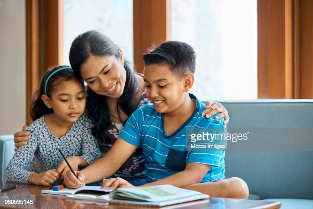 family working on school project at home - malay stock photos and pictures