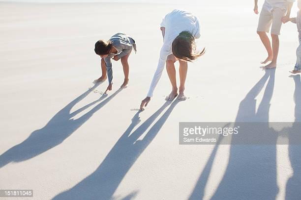 family writing in sand on beach - parte del corpo animale foto e immagini stock
