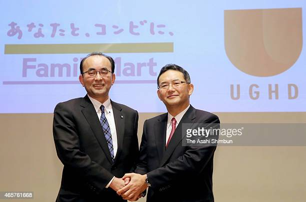 FamilyMart president Isamu Nakayama and Uny Group Holdings President Norio Sako shake hands during a press conference announcing their merger talks...