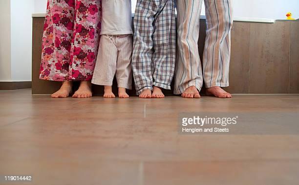 Familys feet in bathroom