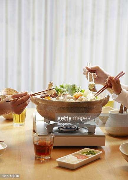 Family's hands eating Japanese hot pot