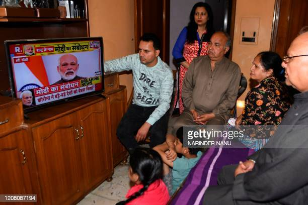 A familywatches Indian Prime Minister Narendra Modi's address to the nation on a television set on a television at their home in Amritsar on March...