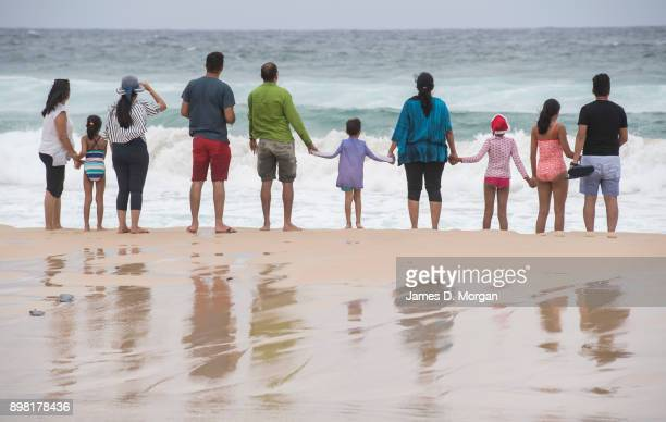 A famliy hold hands as they visit the beach at Bondi on December 25 2017 in Sydney Australia December is one of the hottest months of the year across...