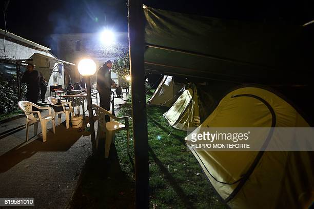 A famly stands in the garden of their house where they set up tents in Cascia on October 31 a day after a 66 magnitude earthquake hit central Italy...