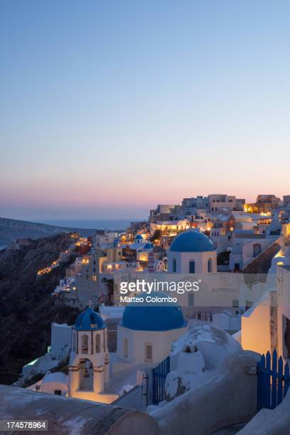 Famous blue domed churches and white buildings in the small greek town of Oia at sunset, in summer. Island of Santorini, Cyclades islands,...