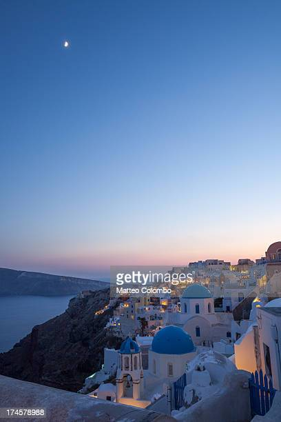 Famous blue domed churches and white buildings in the small greek town of Oia at sunset, in summer, with the moon visible in the colorful sky. Island...