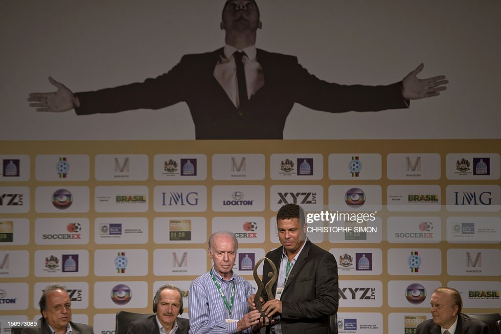 Famous Brazilian former football star Ronaldo Nazario (R), poses with ex football player and coach Mario Jorge Lobo Zagallo after receiving from him a trophy for his career during the opening of the Soccerex football convention, in Rio de Janeiro, Brazil, on November 14, 2012. Soccerex is the leading event provider for the global football industry. AFP PHOTO/Christophe Simon