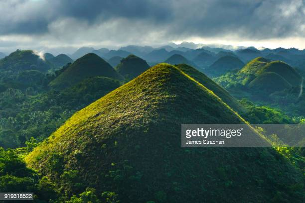 Famous Chocolate Hills face a thunderstorm with one hill outlined by early morning sun, Bohol Island, Philippines