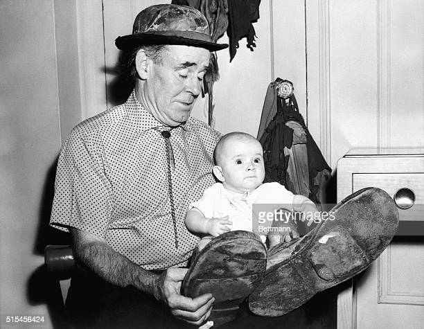 Famous circus clown Emmett Kelly amuses his 5monthold daughter Stasia with his clown hat and outsize shoes as he plays with her at the Hotel...
