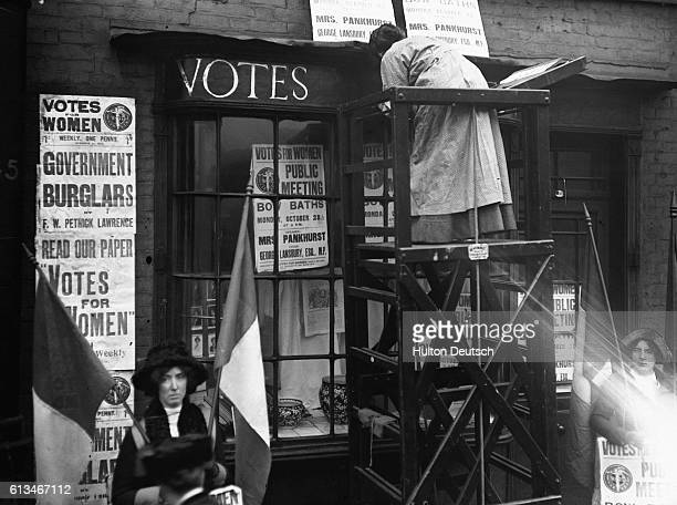 Famous English feminist and socialist Sylvia Pankhurst paints the shopfront of the building that forms the headquarters of the Women's Social Defence...