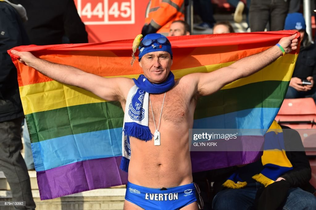 Famous Everton supporter 'Speedo Mick' holds up a rainbow flag in the crowd, in support of Stonewall's rainbow laces campaign during the English Premier League football match between Southampton and Everton at St Mary's Stadium in Southampton, southern England on November 26, 2017. / AFP PHOTO / Glyn KIRK / RESTRICTED TO EDITORIAL USE. No use with unauthorized audio, video, data, fixture lists, club/league logos or 'live' services. Online in-match use limited to 75 images, no video emulation. No use in betting, games or single club/league/player publications. /