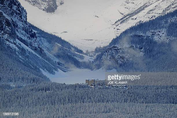 Famous Fairmont Chateau Hotel rests by the frozen Lake Louise in the morning at Lake Louise Alberta on November 24 2012 Lake Louise the famous...