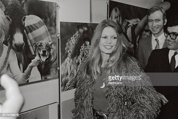 Famous French movie star Brigitte Bardot poses in front of a picture of Brigitte Bardot as she attends the opening of an exhibition where 100 photos...