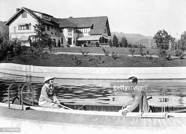 Famous Hollywood couple, Douglas Fairbanks and wife Mary Pickford, canoe along the swimming pool at their Pickfair estate.