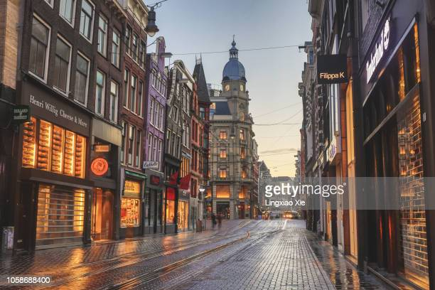 famous leidsestraat street illuminated at dawn, amsterdam, netherlands - city street stock pictures, royalty-free photos & images