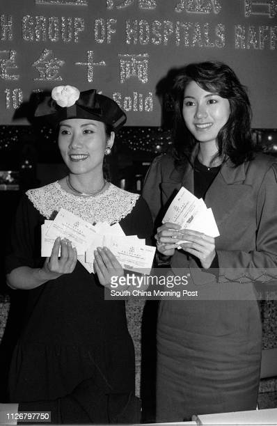 Famous local actress and television personality Liza Wang Mingchun and Miss Hong Kong 1988 Michelle Reis pose for a picture at a raffle ticket sale...