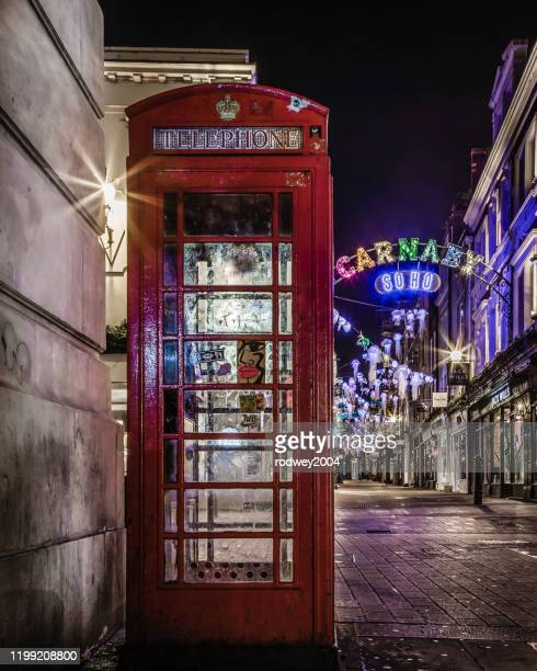 a famous red telephone box near the iconic carnaby street christmas lights - red telephone box stock pictures, royalty-free photos & images