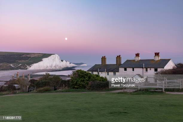 famous seven sisters cliffs and coast guard cottages at sunset, located in east sussex, england, 2018 - cottage stock pictures, royalty-free photos & images