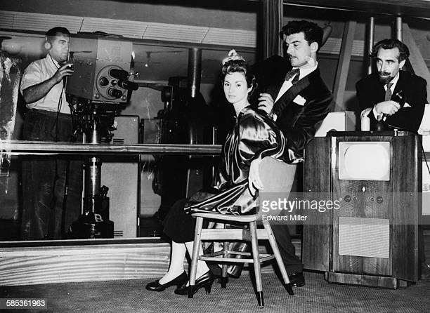 Famous television hairdresser Raymond Bessone known as 'Teazy Weazy' working on the hair of model Brenda in front of a television camera with...