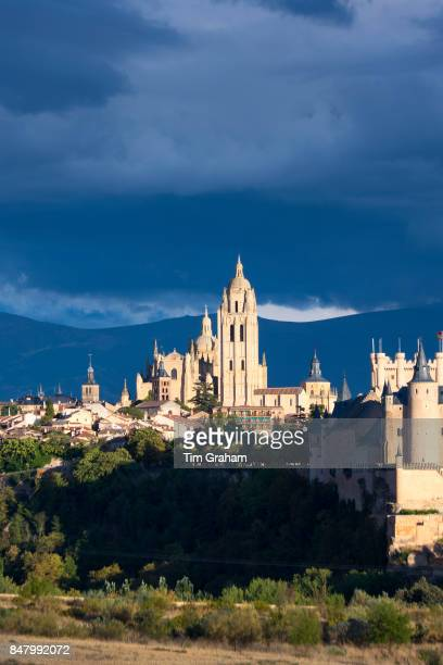 Famous view of Alcazar Castle palace and fortress which inspired Disney castle Cathedral and dramatic sky in Segovia Spain