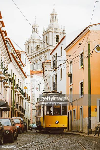 famous yellow tram on the narrow streets of alfama district, lisbon, portugal - tram stockfoto's en -beelden