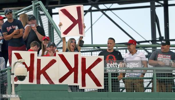 A fan above the centerfield wall holds up a K card to add to the lineup after another strikeout by Boston Red Sox pitcher Chris Sale The Boston Red...
