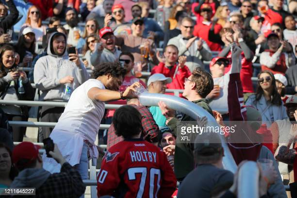 Fan adds a cup to a 'beer snake' during the XFL game between the St. Louis BattleHawks and the DC Defenders at Audi Field on March 8, 2020 in...