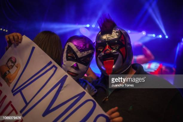 A fan and his father pose for pictures wearing masks during an AAA World Wide Wrestling match on November 16 2018 in Bogota Colombia