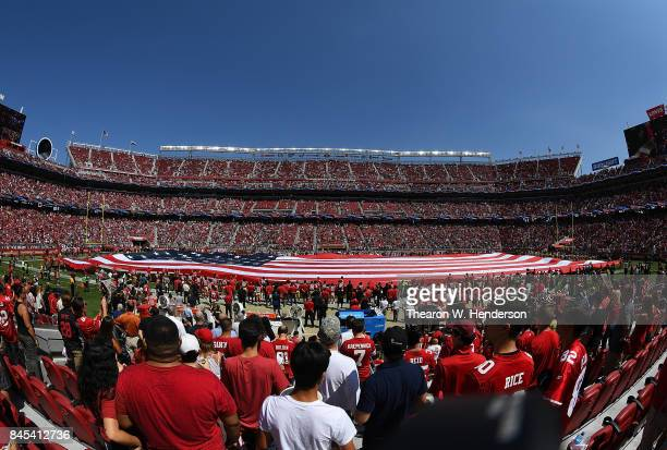 Fan and players stand for the National Anthem prior to the start of an NFL football game between the Carolina Panthers and San Francisco 49ers at...