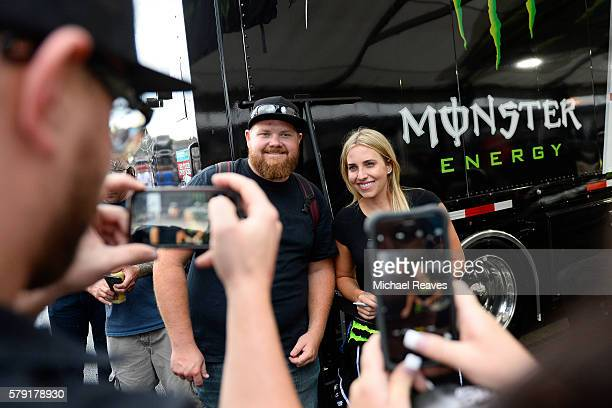 Fan Anthony Colletti gets his photo with driver Brittany Force during a rain delay at day one of the Mo-Par Mile High Nationals at Bandimere Speedway...
