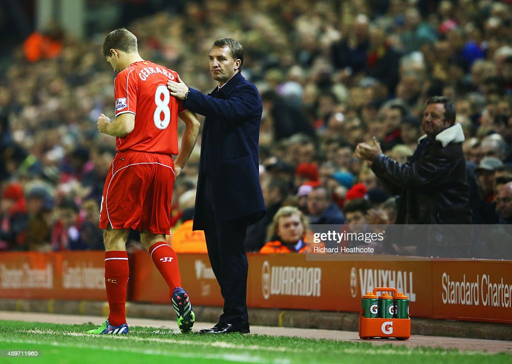 A fan applauds as Steven Gerrard of Liverpool prepares to come onto the pitch as a substitute alongside Brendan Rodgers manager of Liverpool during the Barclays Premier League match between Liverpool and Stoke City at Anfield on November 29, 2014 in Liverpool, England.