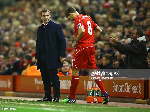 A fan applauds as Steven Gerrard of Liverpool prepares to come onto the pitch as a substitute alongside Brendan Rodgers manager of Liverpool during...