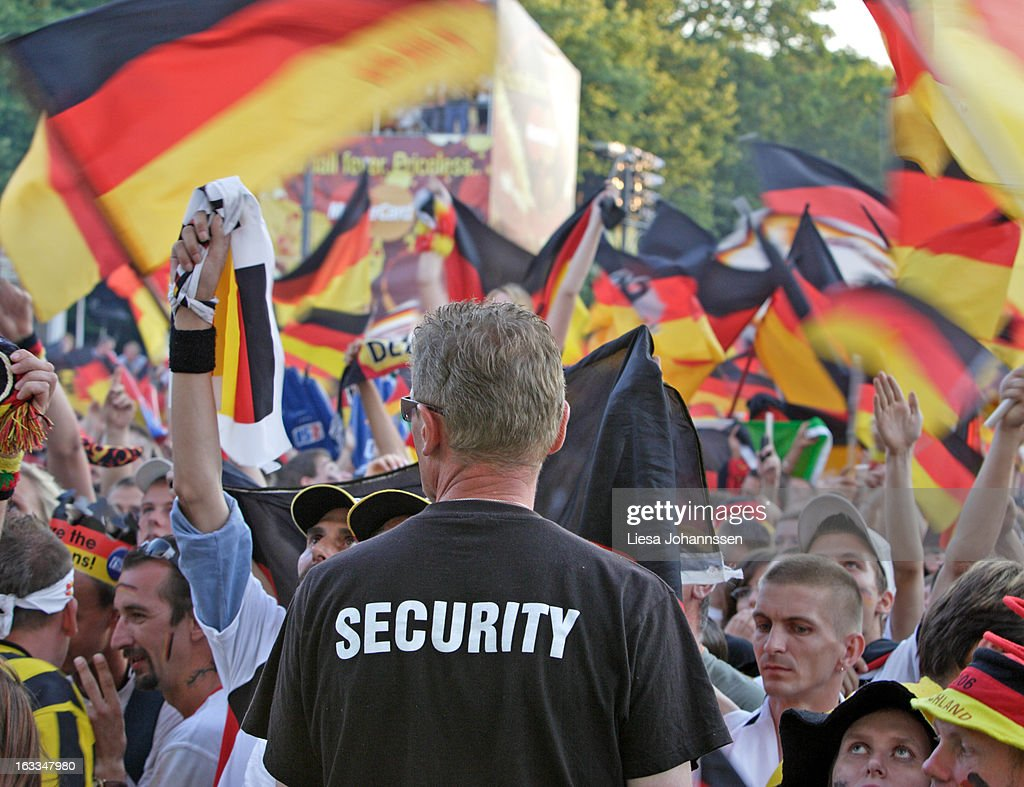Fan area in Berlin during the FIFA World Cup 2006, International Soccer Tournament, Crowd cheering for the German Team, Men and Women bellowing and swinging flags, Security from behind, Standing and watching the crowd, July 05, 2006, Berlin , Germany.