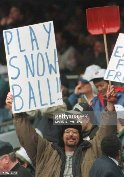 A fan at Yankee Stadium holds up a sign and a snow shovel as a light snow began to fall before the start of the Yankees' home opener against the...