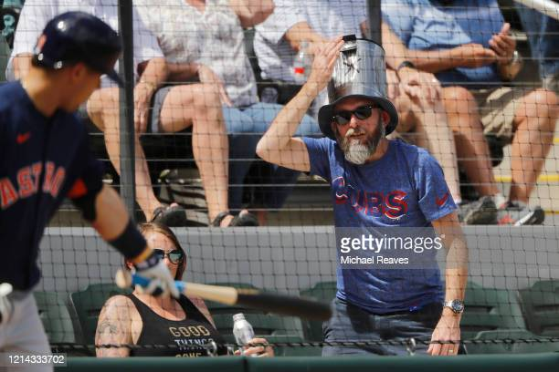 A fan bangs on his hat in the shape of a trash can as Aledmys Diaz of the Houston Astros looks on from the on deck circle against the Atlanta Braves...