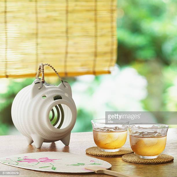 Fan, barley tea and mosquito coil on table