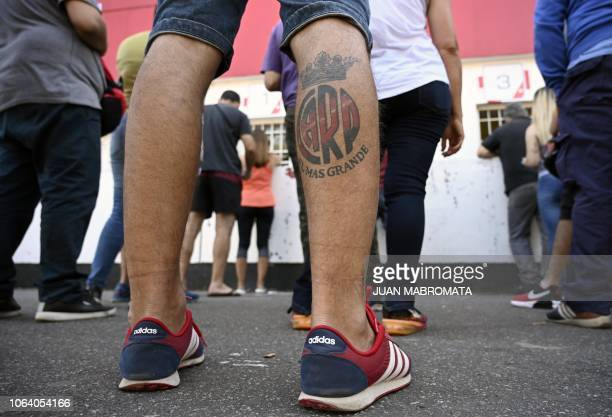 A fan bearing a River Plate's emblem tattooed on his calf waits in line at the box office of the Monumental stadium in Buenos Aires on November 21...