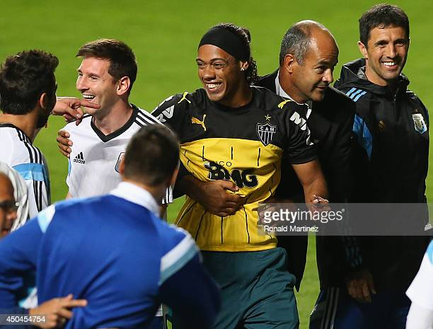 A fan bearing the resemblance of Ronaldinho is escorted off the field while talking to Lionel Messi of Argentina after an open trainging session...