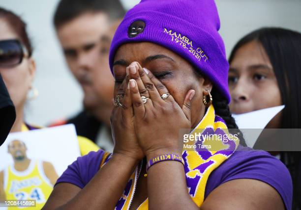 A fan becomes emotional while watching a live broadcast of the 'Celebration of Life for Kobe and Gianna Bryant' memorial service on a fan's iPad...