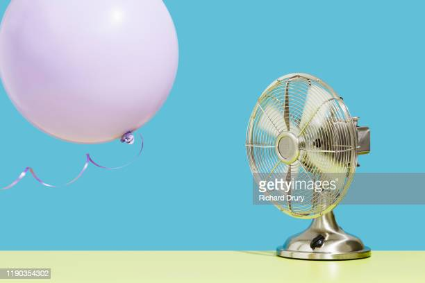 fan blowing balloon - assistance stock pictures, royalty-free photos & images