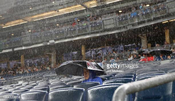 A fan braves the rain during a delayed start of a game between the New York Yankees and the New York Mets at Yankee Stadium on July 22 2018 in the...