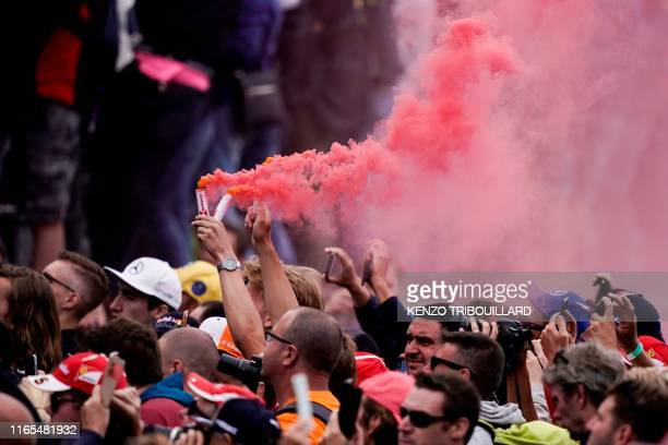 Fan burns smoke bombs or flares as the best three drivers celebrate on the podium after the Belgian Formula One Grand Prix at the Spa-Francorchamps...