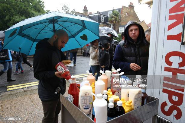 A fan carefully balances his umbrella as he puts ketchup on his chips in the rain ahead of the Premier League match between Fulham FC and Burnley FC...