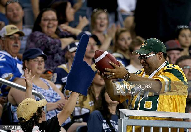 A fan catches a ball thrown by AJ Guyton of the Edmonton Eskimos after he scored a touchdown against the Winnipeg Blue Bombers during a CFL football...