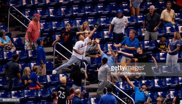 A fan catches a foul ball during the game between the Miami Marlins and the New York Mets at Marlins Park on September 19 2017 in Miami Florida via...